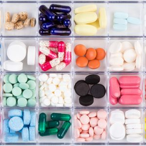 Various medicine pills and capsules in plastic container